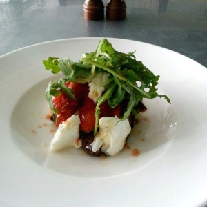 Mozzarella salad with arugula, peppers and eggplant.