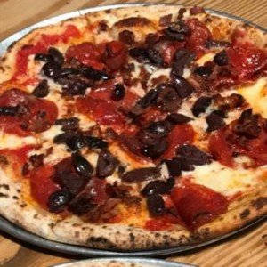 pizza de aceitunas negras y tomates al filetto con bacon.